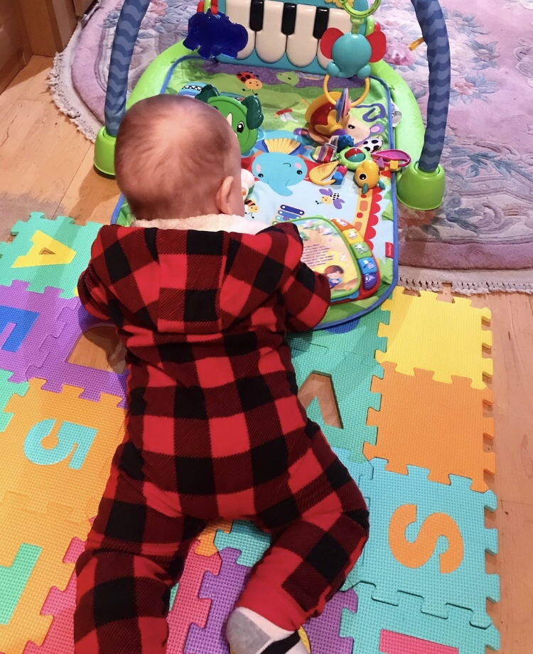 baby lying on play mat with toys