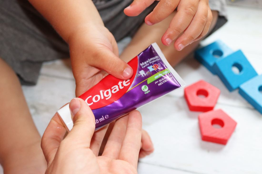 mum and toddler holding tooth paste