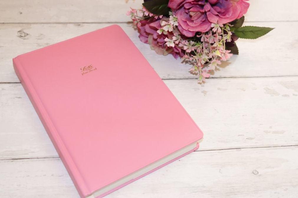 pink planner on desk
