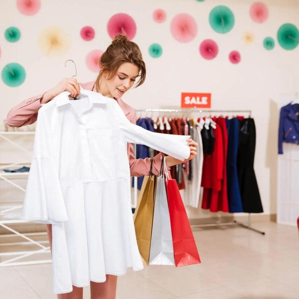 Young girl in pink pantsuit with colorful shopping bags in hands choosing clothes in fashion boutique. Beautiful smiling girl go shopping and choose white dress in clothes store