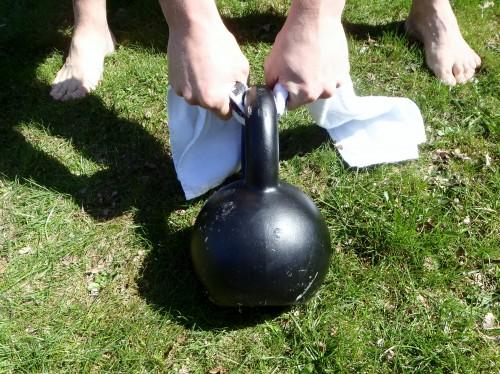Handduksswing med kettlebell: Greppa handduken nära kettlebellens handtag.