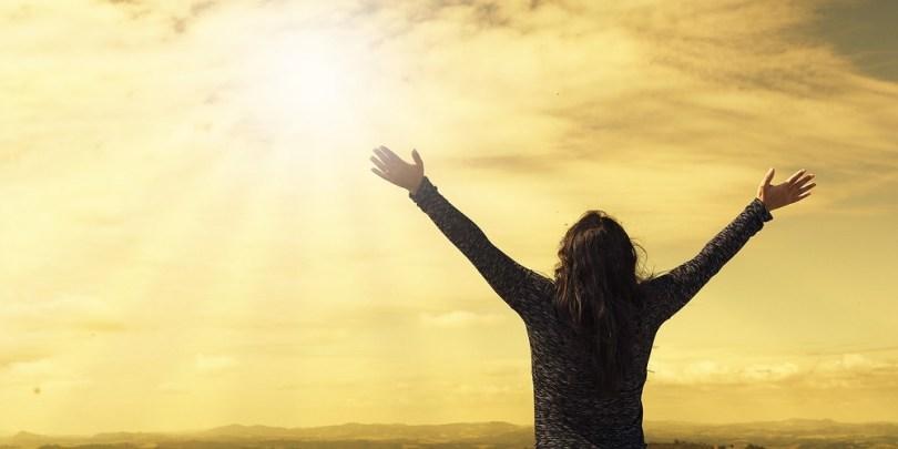 Mulher com os braços abertos e expressando sua gratidão à tudo.