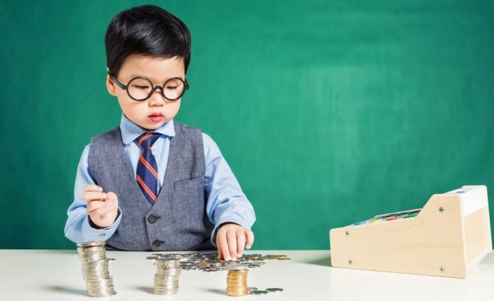 Menino mexendo com moedas que ele recebeu dos pais como mesada educativa.
