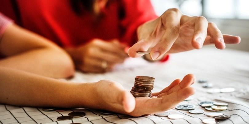Mulher dando moedas na mão do filho e o ensinando sobre o dinheiro.