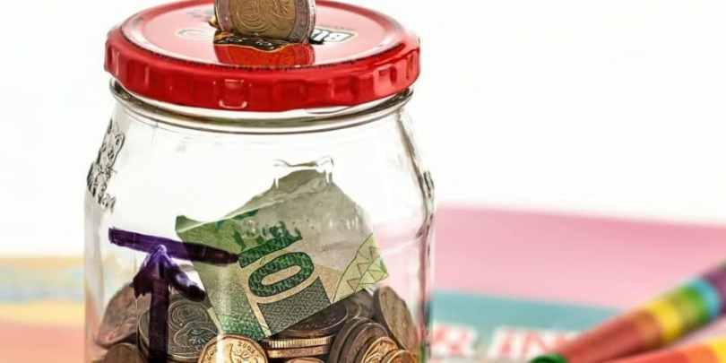 Dinheiro sendo colocado num pote, indicando um caminho pras crianças gerenciarem a mesada.