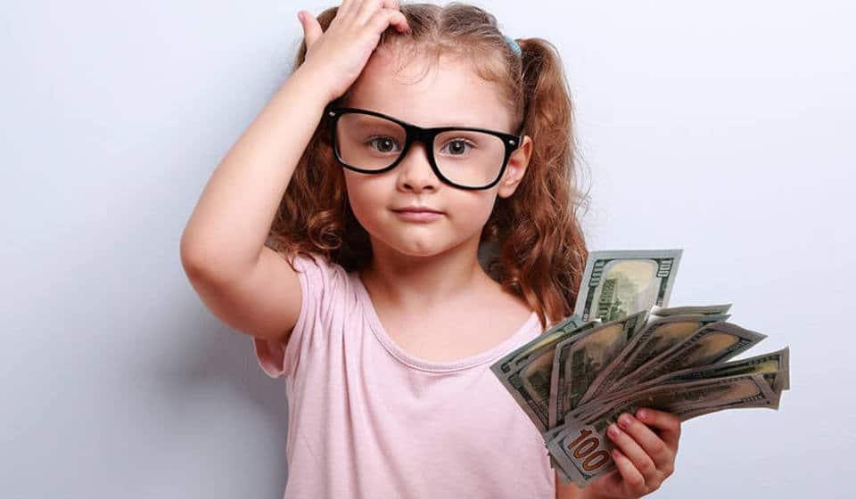 Menina com dinheiro na mão, esperando por educação financeira infantil pra saber o que fazer com ele.