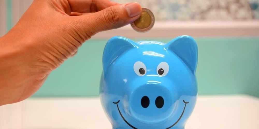 Pessoa colocando moeda num porquinho, geralmente utilizado pra poupar dinheiro.