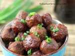 Crockpot meatballs in a bowl with fresh green onion slices on top.