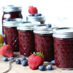 Mason jars Canned with Mixed Berry Jam. Strawberries and blueberries sound them.