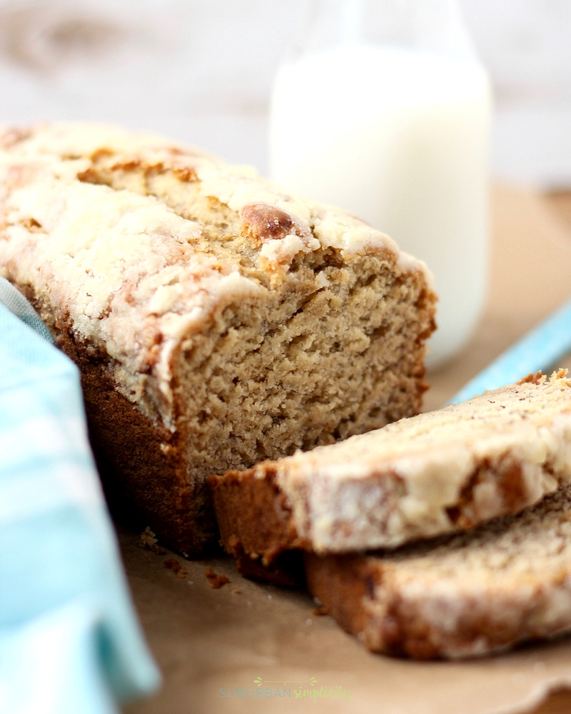 Banana bread with a crumbly topping cut and ready to eat. With a glass of milk in the background.