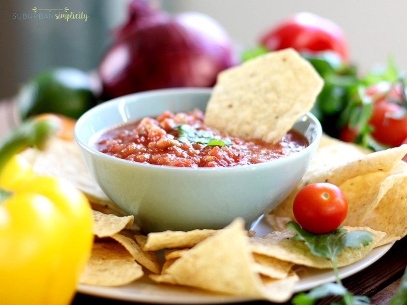 Chips and salsa in a blue bowl surrounded by fresh peppers and onions.