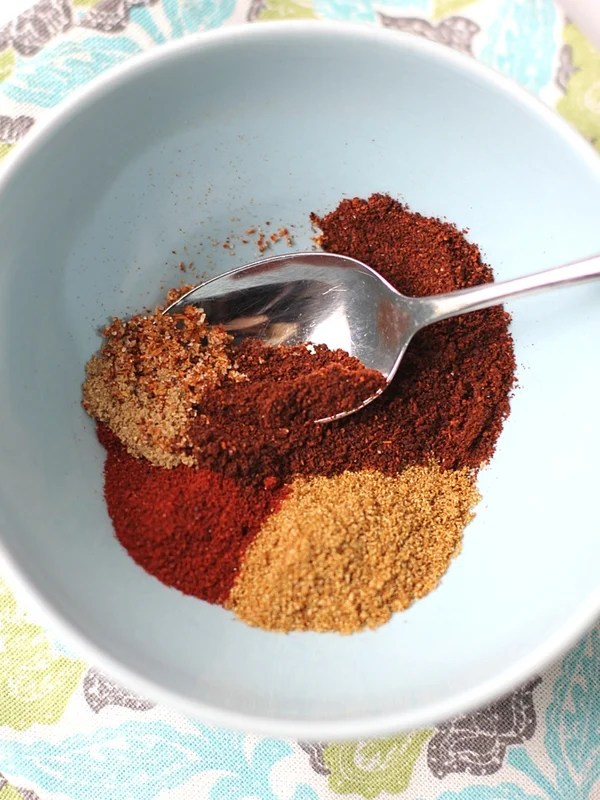 Spices for Chicken Fajitas in a small blue bowl with a spoon.
