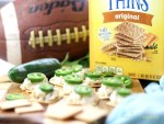 Wheat Thins with a cheesy dip topped with a jalapeño pepper.