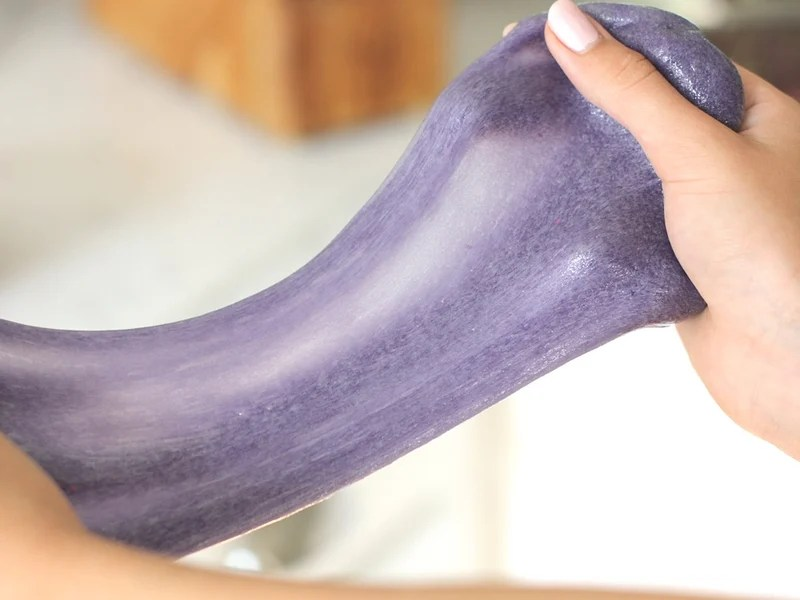 Purple slime being stretched by a girls hands.