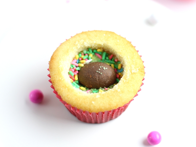 Vanilla cupcakes hollowed out with a Butterfinger NestEgg and sprinkles inside.