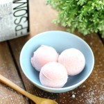 DIY Bath Bomb Recipe with three bath bombs sitting in a bowl.