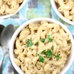 macaroni and cheese made in the instant pot in a bowl with garnish on top.