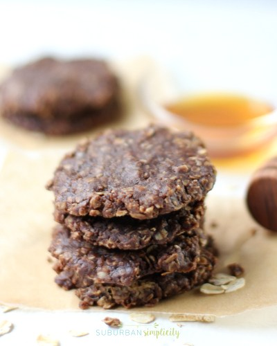 Stacked no bake chocolate cookies with honey in the background.