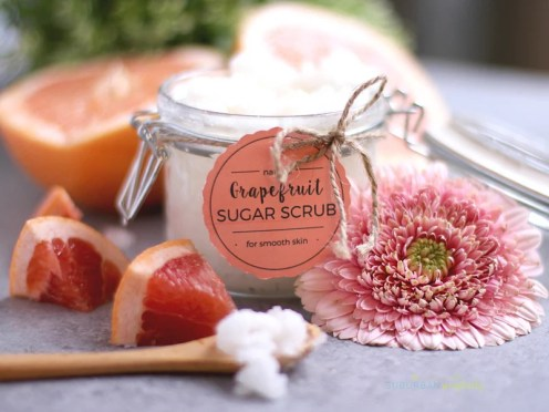 A freshly made jar of grapefruit sugar scrub with fresh grapefruit next to it.