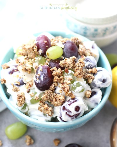 Creamy grape salad in a bowl with toppings.