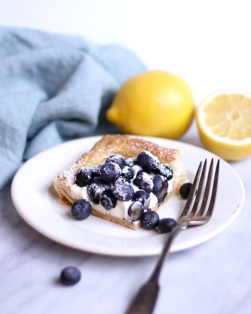 Blueberry tart on a plate with a fork.