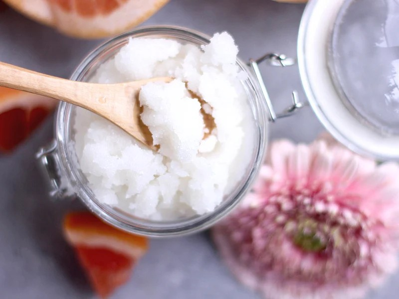 Top view of a jar of grapefruit sugar scrub with a flower next to it.