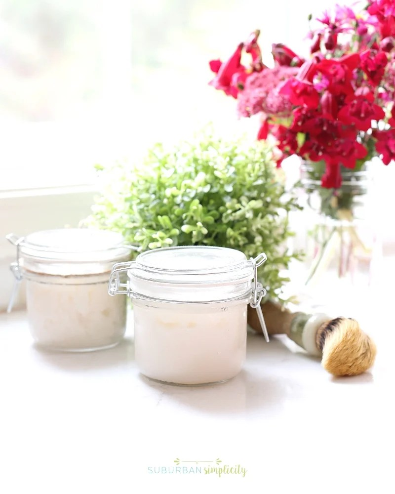 Jar of sugar scrub on the counter with flowers in the background.