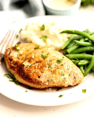 Baked Parmesan Pork Chops on a plate with green beans.