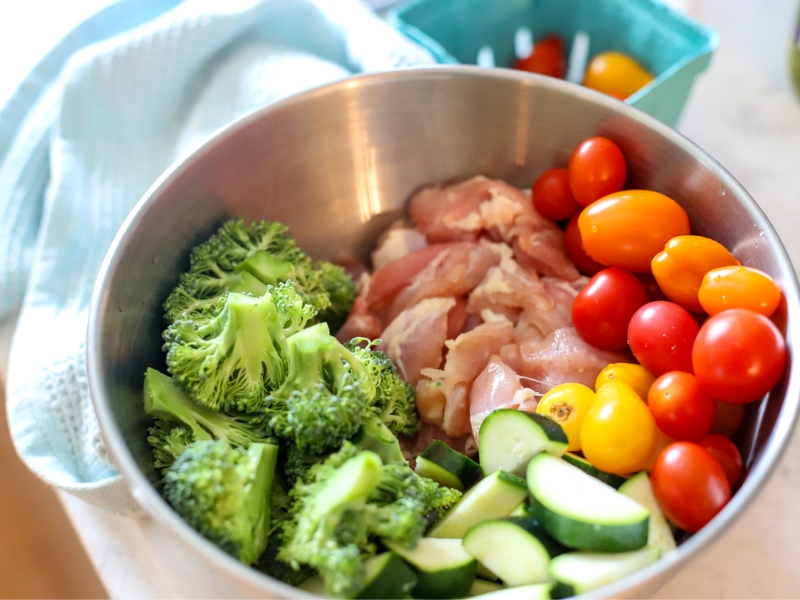 Chicken, broccoli, tomatoes and zucchini in a bowl.