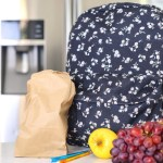 Backpack on kitchen counter with fruit.