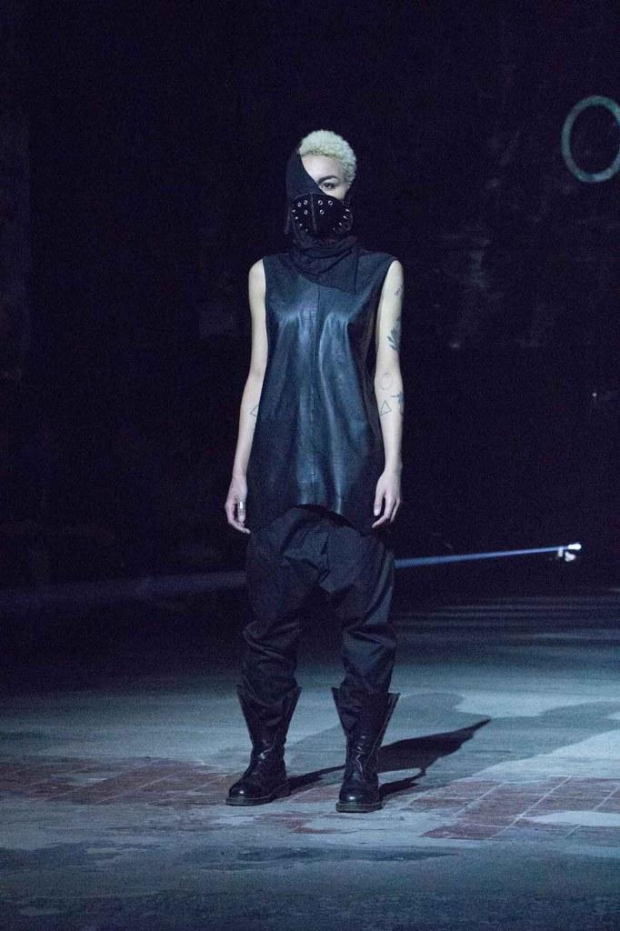 A model wearing all black on the runway in Berlin.