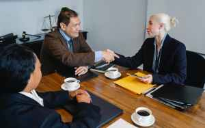 cheerful colleagues shaking hands after deal