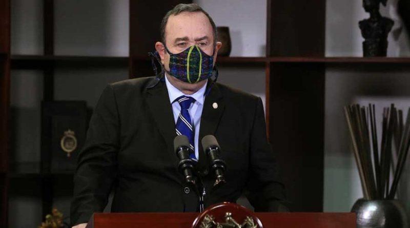 Presidente de Guatemala Alejandro Giammattei, con saco negro y mascarilla negra, dando declaraciones en cadena nacional
