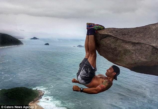 صور مذهلة لرجل معلق من قدمه على سطح جبل من ارتفاع 1000 قدم بالبرازيل