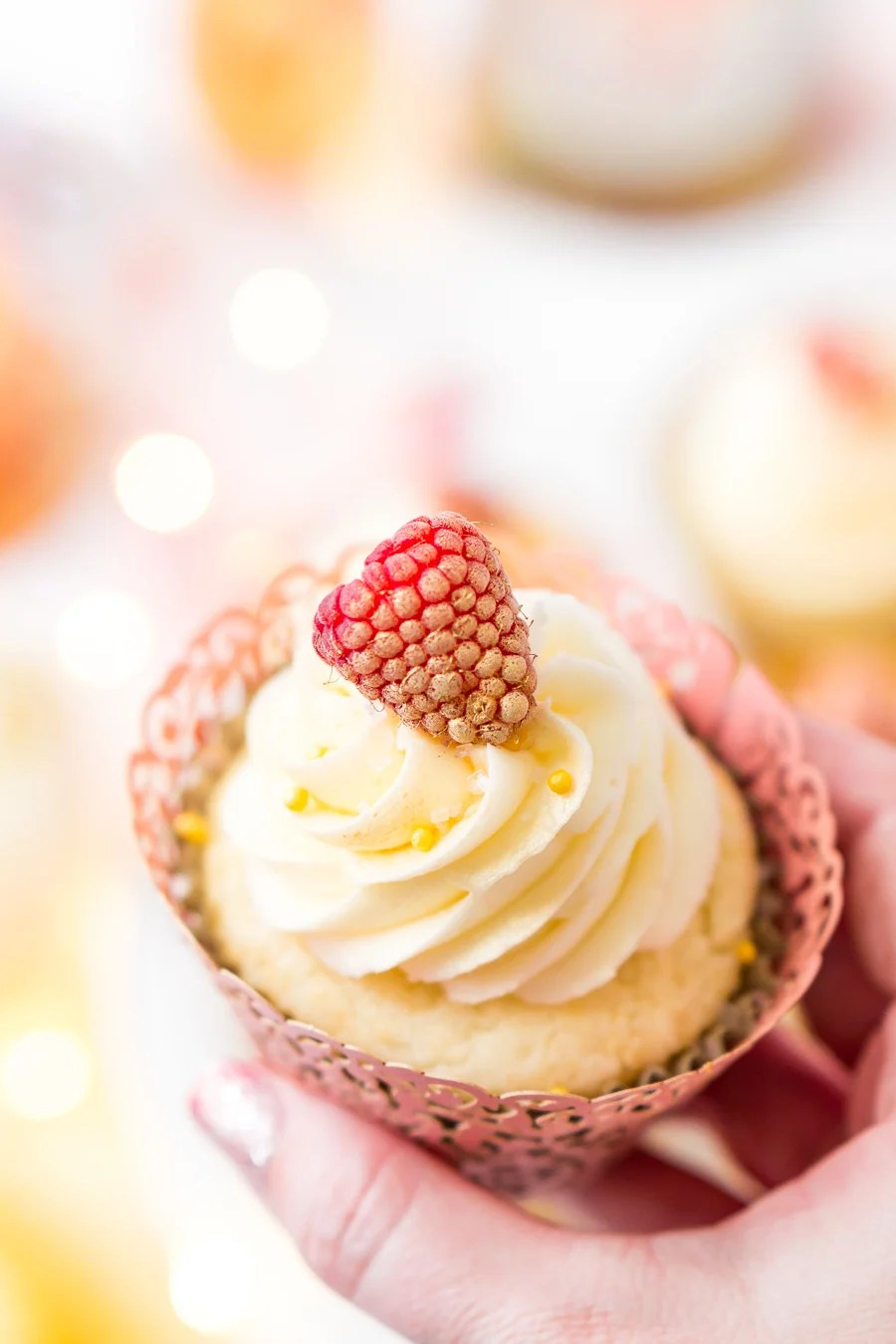 These White Chocolate Raspberry Champagne Cupcakes are perfect for New Year's Eve, Bridal and Baby Showers, and Valentine's Day! Light and fluffy white chocolate cake filled with raspberry filling and topped with a luscious champagne buttercream!