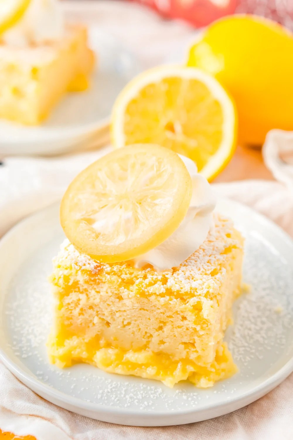 Lemon Cake on small white plate with lemon in the background.