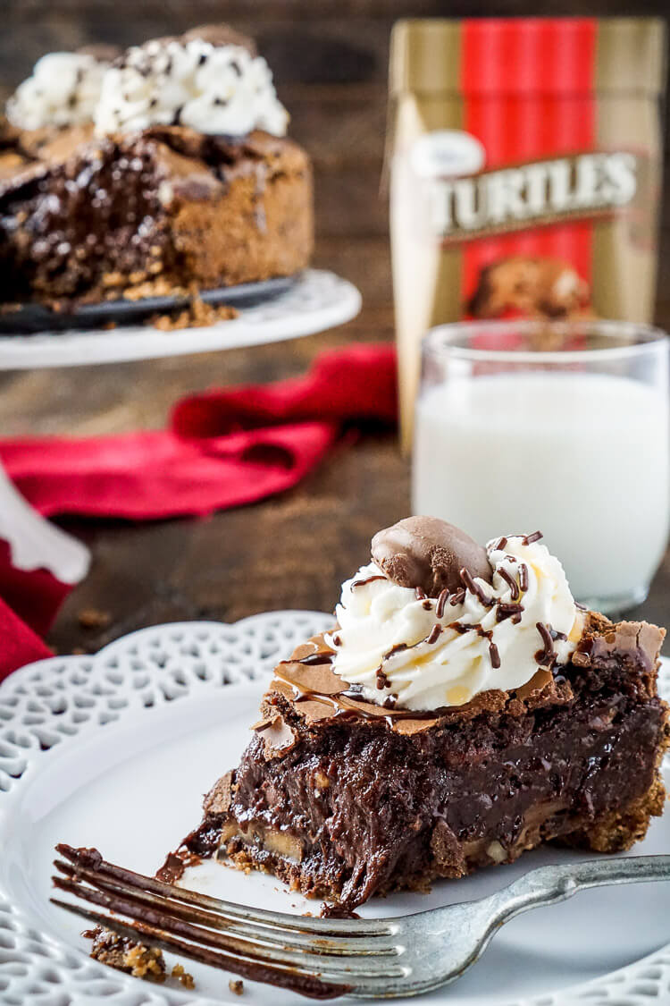 This Gooey TURTLES Brownie Pie is the ultimate comfort dessert! A brownie baked into a graham cracker crust and laced with TURTLES® clusters and pecans, then topped with whipped cream and both caramel and chocolate drizzle! Can you say YUM!