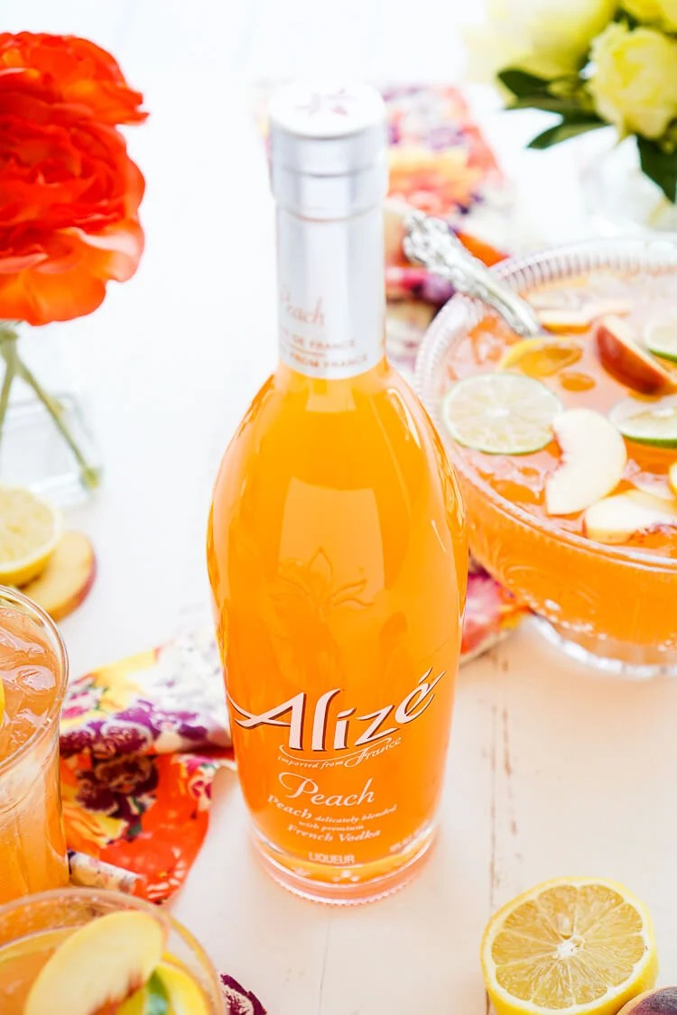 This Peach Rum Punch is the perfect big batch cocktail for summer! Smooth Alizé Peach vodka blends with white rum, lime juice, and ginger ale for a refreshing and vibrant warm weather beverage!