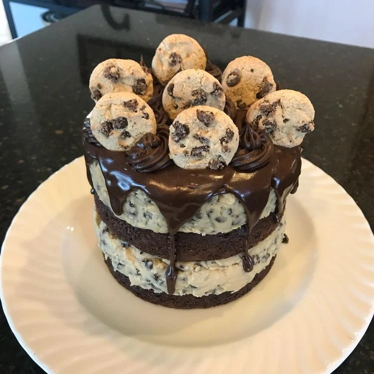 This Chocolate Chip Cookie Dough Cake is made with two layers of delicious chocolate cake, and two layers of edible cookie dough then topped with ganache, frosting, and mini chocolate chip cookies!