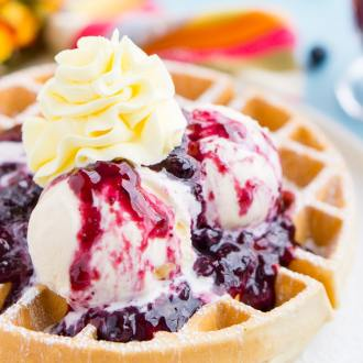 Belgian Waffles with Mango Blueberry Compote are a flavorful and fun brunch dish! Fluffy waffles, vibrant wild blueberries, and luscious mangoes, topped with ice cream and whipped cream!