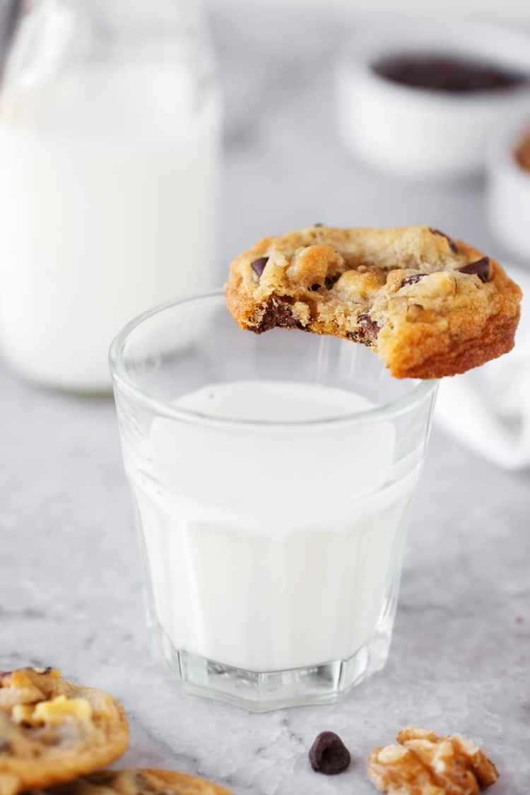 Toll House Cookie with bite out of it on glass of milk