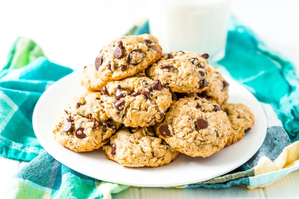 Lactation Cookies on a white plate on a blue and green napkin with a glass of milk in the background.