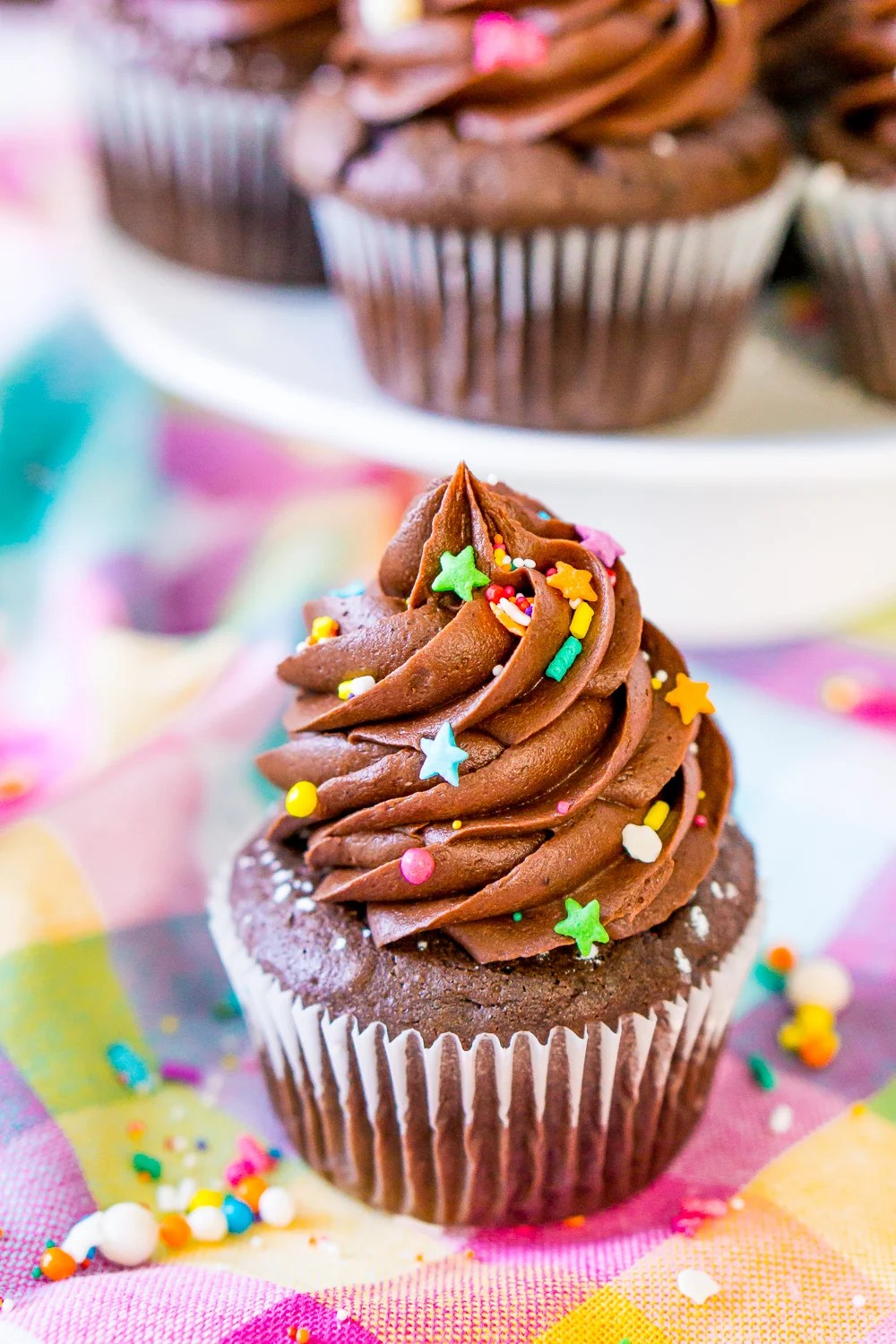 Chocolate Cupcake with Chocolate Buttercream Frosting on colorful napkin with colorful sprinkles