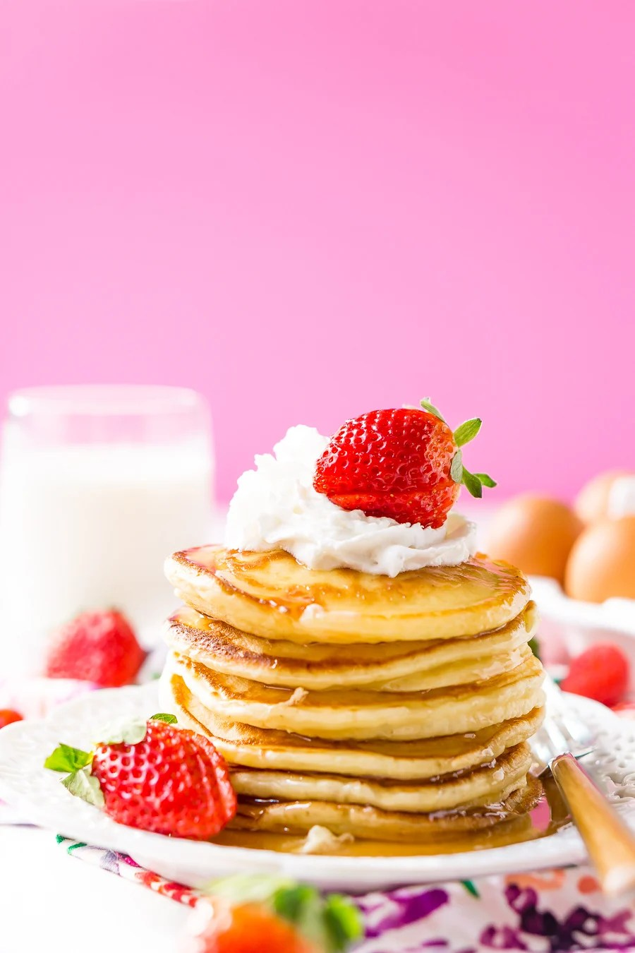 Cream Cheese Pancake Stack on white plate with berries and whipped cream with pink background and floral napkin.