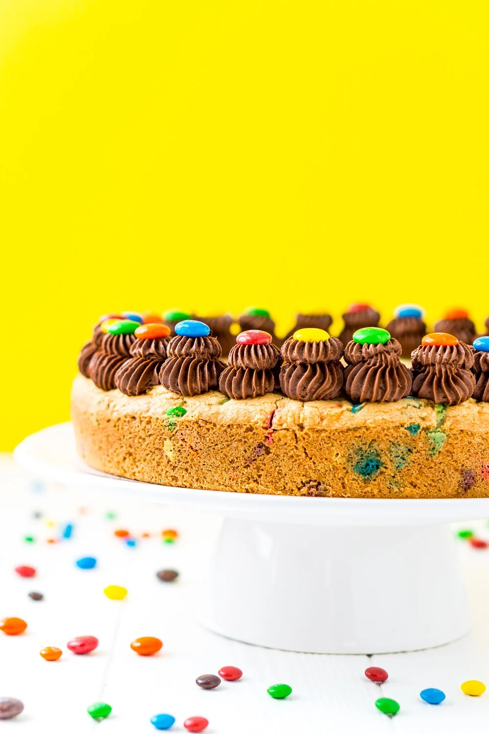 M&M's Cookie Cake with chocolate frosting on a white cake stand with yellow background.