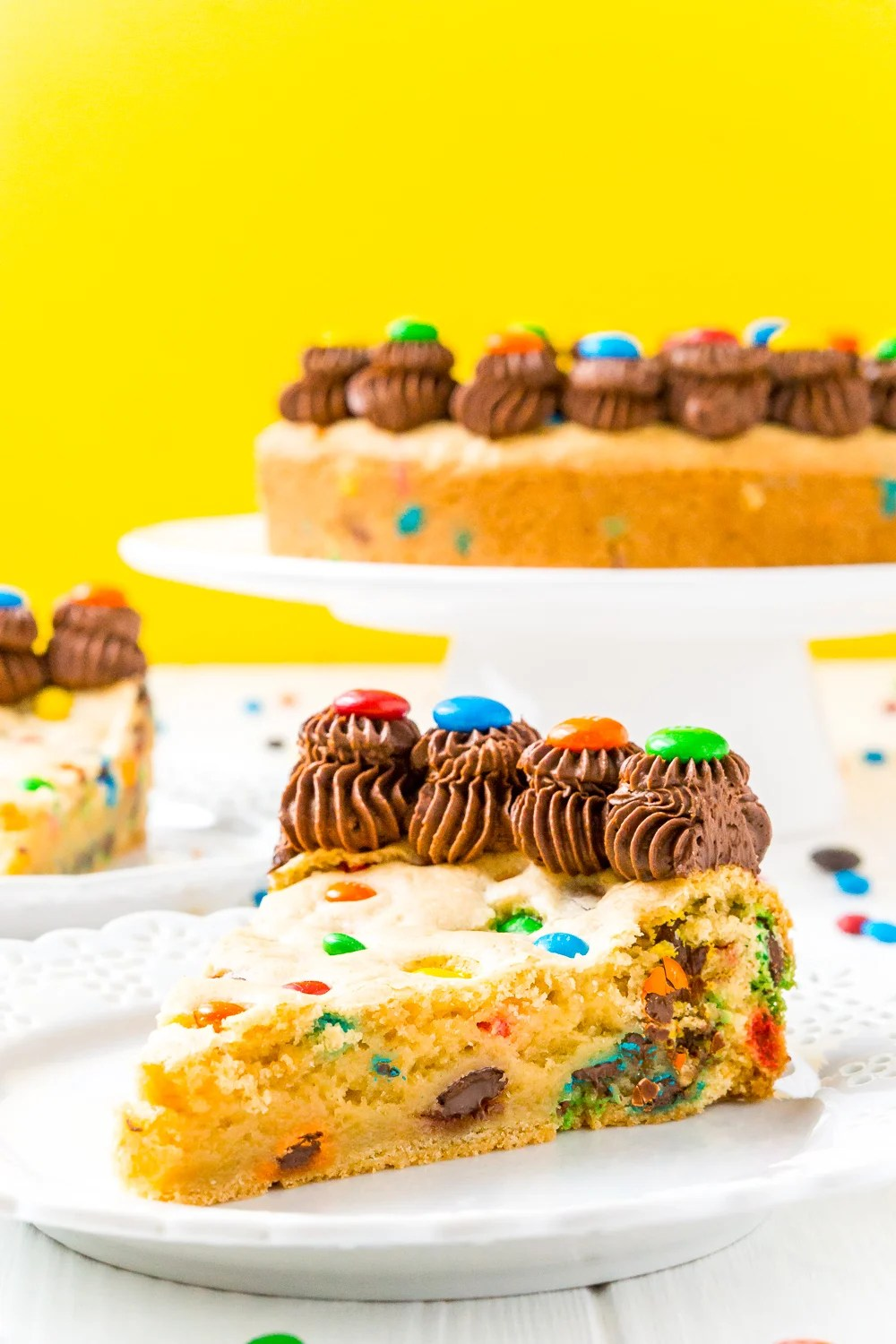 Slice of M&M's Cookie Cake on white plate with rest of cake in the background.