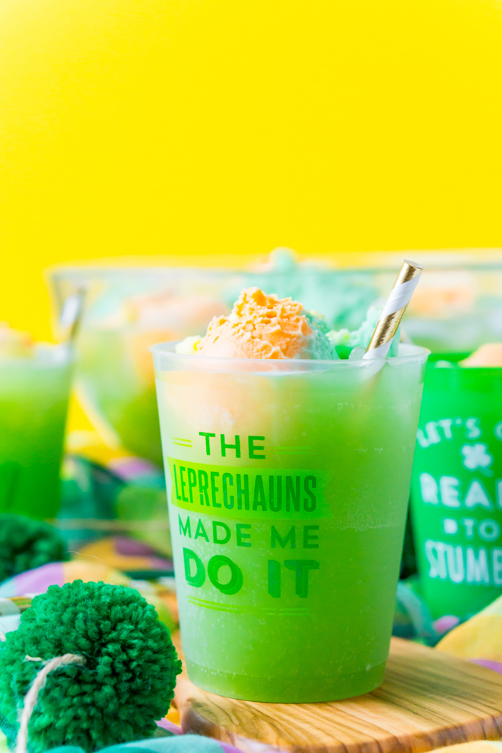"""Cup of St. Patrick's Day Punch that says """" The Leprechauns Made Me Do It"""" on a wood board with a punch bowl and more cups in the background."""
