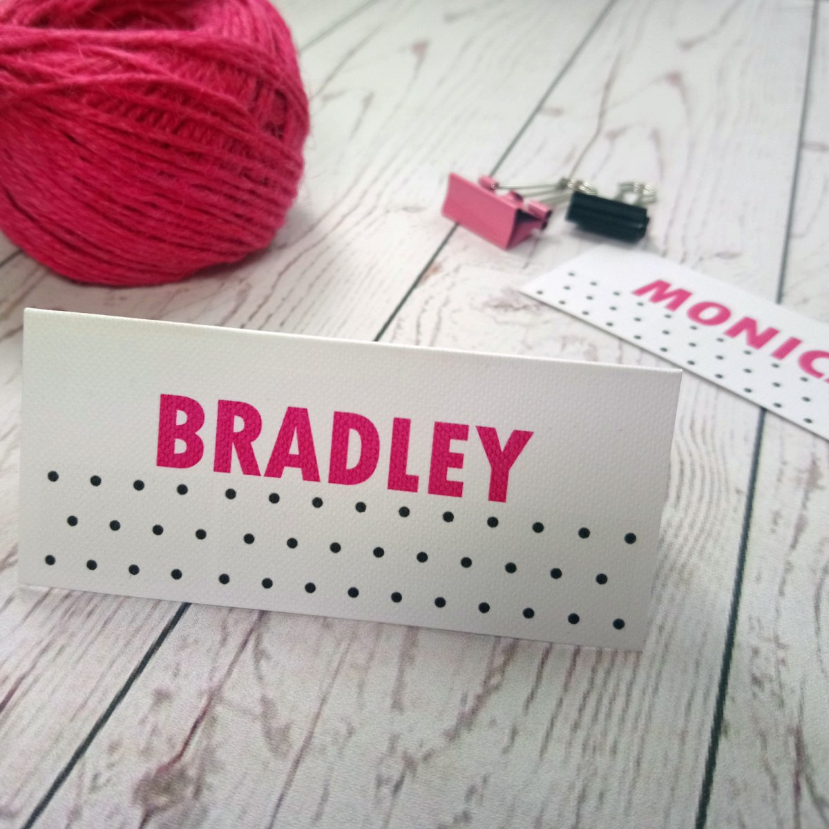 Polka Dot Place Cards. Generic Picture with pink guest names and black polka dots on white textured card