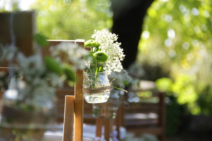 Glass Jar with flowers tied to reception chair with rustic twine