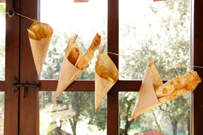 rustic paper cone pork scratching hanging off a twine. Handmade wedding food